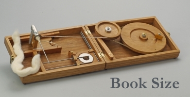 Book size spinning charkha with piece of wool