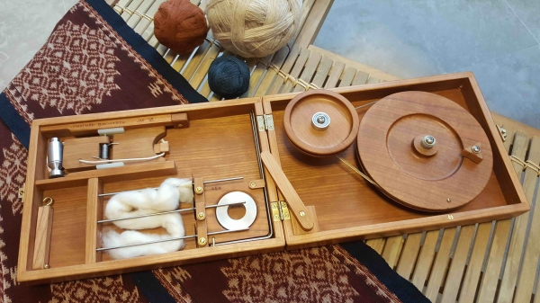 book-size charkha open with a piece of wool ready for spinning